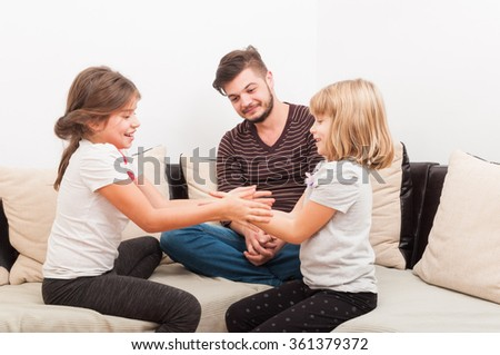 Young handsome father and two beautiful daughters having family time in the living room - stock photo