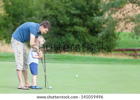 young handsome father teaching his little son how to play golf - stock photo