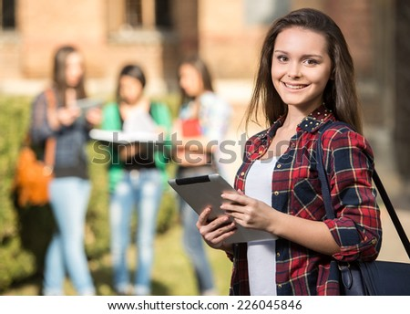 Young handsome female student at the college, outdoors. Her classmates in the background. - stock photo
