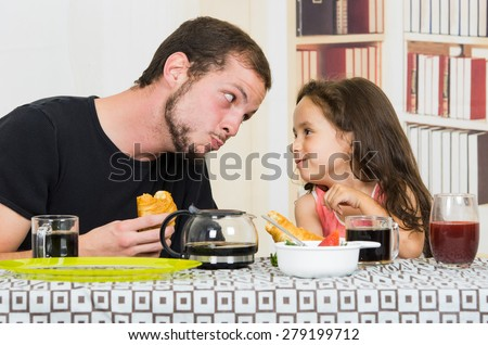 Young handsome fun loving dad having breakfast with small daughter - stock photo