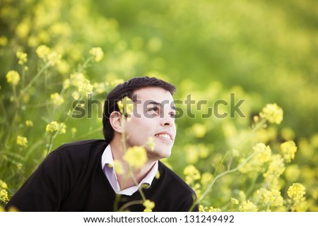 Young handsome guy on field showing hopeful facial expression - stock photo