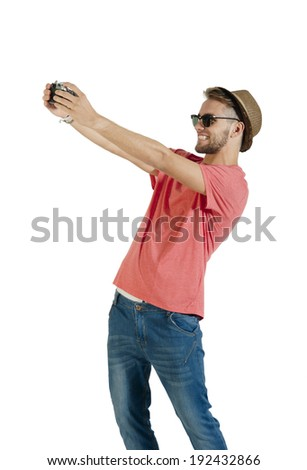 Young handsome guy taking selfie with film camera - stock photo