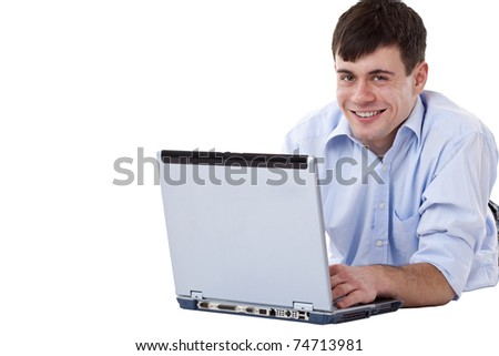 Young, handsome, happy man lying on floor with computer. Isolated on white background. - stock photo