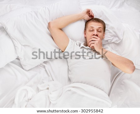 Young handsome happy man waking up on bed, top view - stock photo