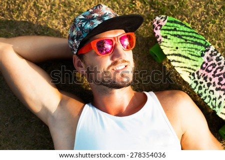 Young handsome hipster man relaxed and  lay at sunny day on the park on tropical island in cool summer sunglasses,reflecting palm trees in sunglasses.Stylish young beard man,hipster outfit. - stock photo