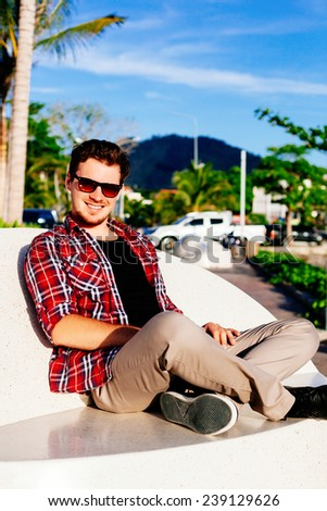 Young handsome hipster man relaxed at sunny day on island park, amazing view on mountains and palms, wearing stylish plaid shirt and sunglasses, enjoy his holiday.