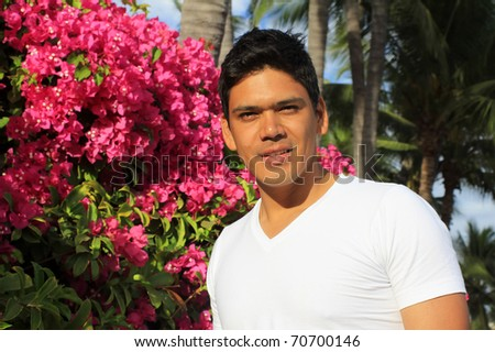 Young handsome hispanic man standing in front of Bougainvillea flowers and palm trees - stock photo