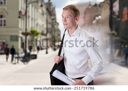 Young handsome late architect hurrying to work - stock photo