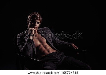 Young handsome macho man with muscle abdominal and open jacket sitting in armchair.