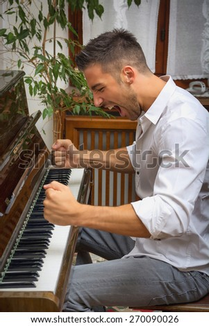 Young handsome male artist playing his wooden classical upright piano, shouting unhappy and frustrated