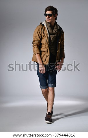 Young handsome male in shorts with sunglasses posing in full length over light background - stock photo