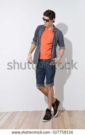 Young handsome male in shorts with sunglasses posing in full length over wooden background - stock photo