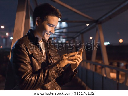 Young handsome male in the city using his smartphone.  - stock photo