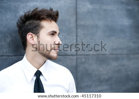 Young handsome man against wall - stock photo