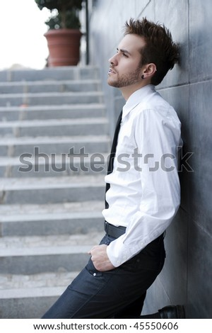 Young handsome man against wall (piercing in lips) - stock photo