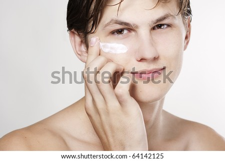 Young handsome man applying cream - stock photo