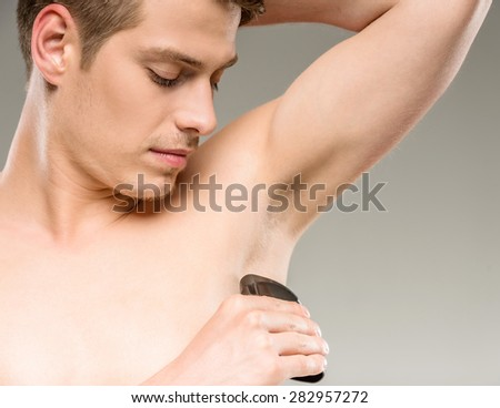 Young handsome man applying deodorant on armpits. - stock photo