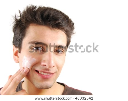 young handsome man applying face cream (over white background) - stock photo