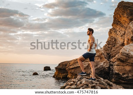Young handsome man athlete standing at the rocky beach by the sea