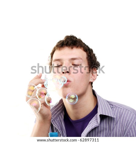 young handsome man blowing bubbles - stock photo