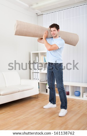 Young Handsome Man Carrying Rolled Carpet In Living Room - stock photo