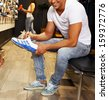 Young handsome man choosing sport footwear in sport outlet - stock photo