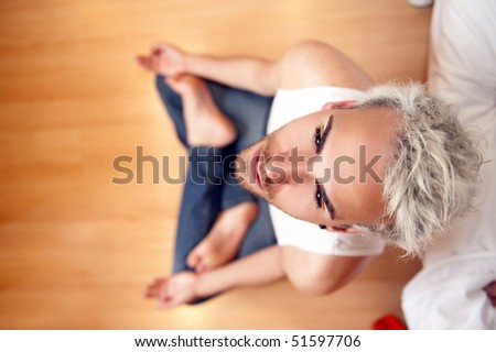 Young handsome man doing yoga on the floor - stock photo