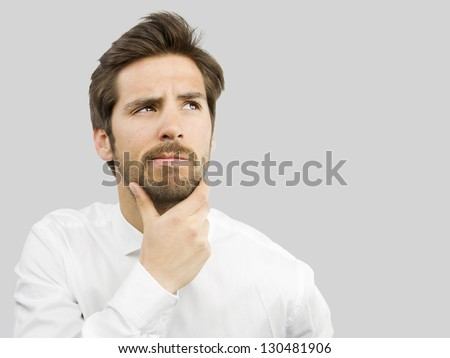 young handsome man doubting isolated over gray background - stock photo