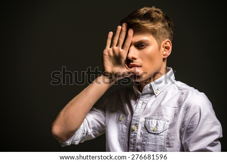Young handsome man dressed casual posing in the studio on dark background. Fashion portrait. - stock photo