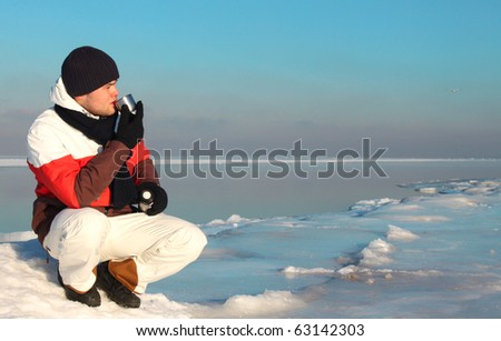 Young handsome man drinks tea/coffee on winter seaside