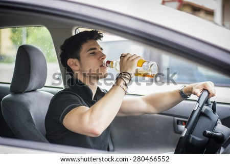 Young handsome man driving his car while drinking alcohol in the traffic - stock photo