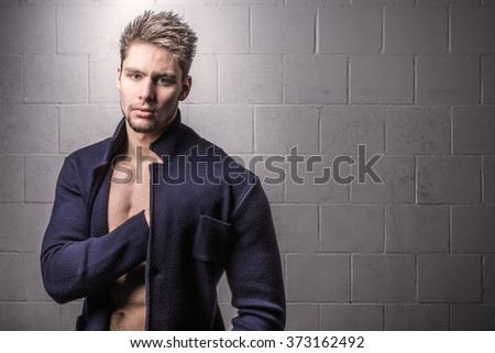 Young handsome man elegant against white brick wall fashion portrait - stock photo