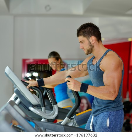 young handsome man exercising in the gym - stock photo