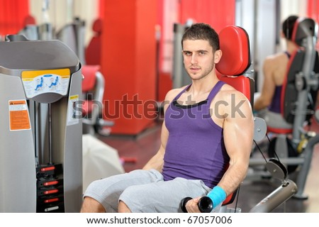 young handsome man exercising in the gym