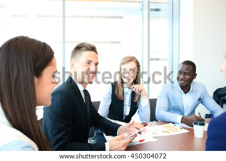 Young handsome man gesturing and discussing something while his coworkers listening to him sitting at the office table