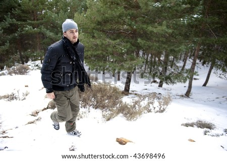 Young handsome man going up in winter landscape - stock photo
