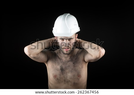 young handsome man in a dirty helmet - stock photo