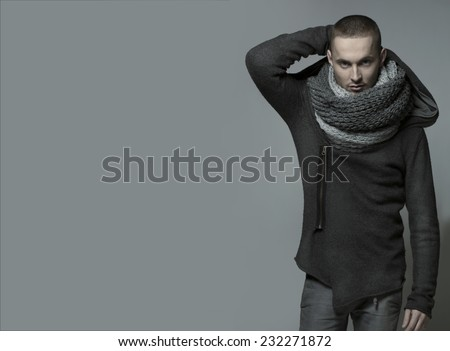 Young handsome man in a grey wrap, shawl - stock photo