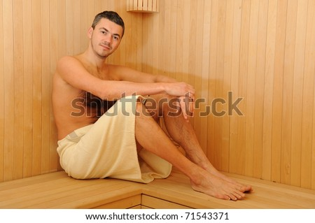 Young handsome man in a towel relaxing in a russian wooden sauna - stock photo