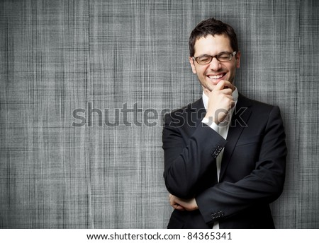 Young handsome man in black suit and glasses laughing against gray textured wall