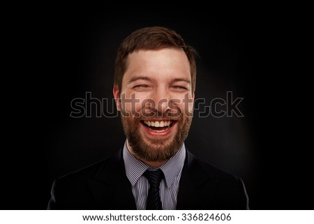 Young handsome man in black suit laughing against  black background