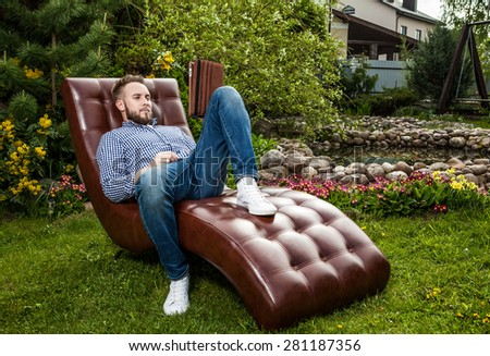 Young handsome man in casual clothes sit in luxury sofa with iPad in summer garden.