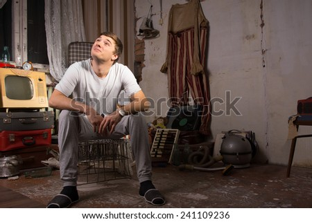 Young Handsome Man in Casual Shirt Sitting on Cage at Messy Junked Room Looking Up - stock photo