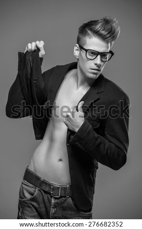 Young handsome man in glasses and tuxedo posing in the studio. Black and white fashion portrait. - stock photo