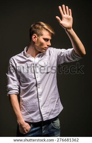 Young handsome man in shirt and jeans posing in the studio on dark background. Fashion portrait. - stock photo