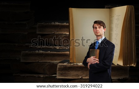 Young handsome man in suit reading old book