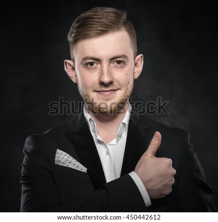 Young handsome man in suit smiling on dark background. - stock photo