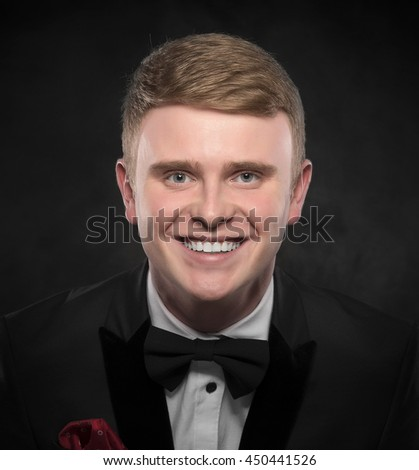 Young handsome man in suit with bow-tie smiling on dark background.