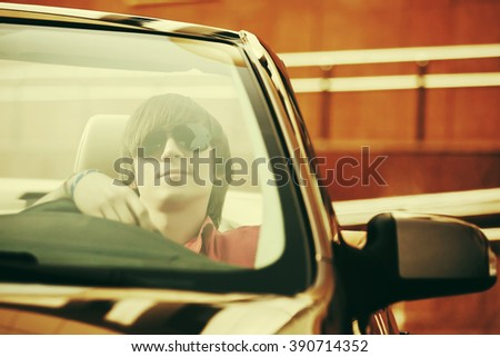 Young handsome man in sunglasses driving convertible car - stock photo
