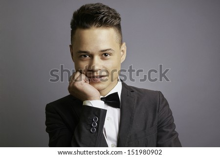 Young handsome man in tuxedo, hand holding the chin, smiling, gray background, studio shoot. - stock photo